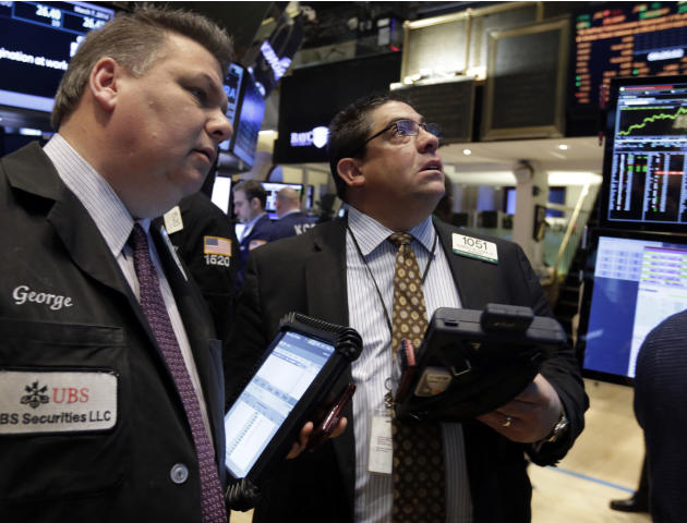 Traders George Ettinger, left, and Robert Oswald work on the floor of the New York Stock Exchange Friday, March 7, 2014. Stocks were wavering between small gains and losses early Friday after the gove