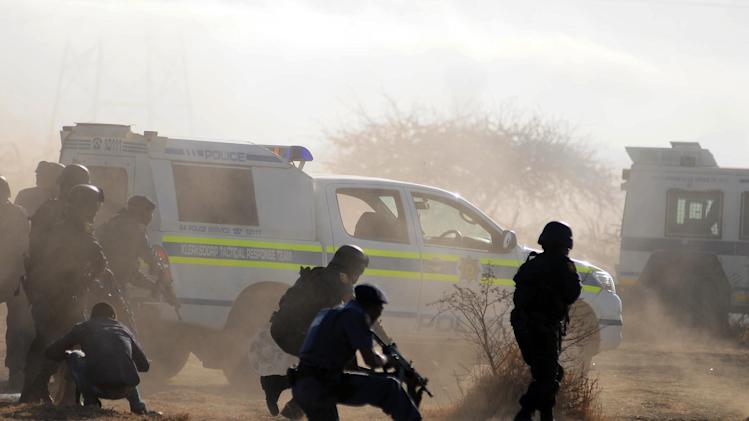 Policemen in teargas and dust open fire on striking miners at the Lonmin Platinum Mine near Rustenburg, South Africa, Thursday, Aug. 16, 2012. South African police opened fire Thursday on a crowd of striking workers at a platinum mine, leaving an unknown number of people injured and possibly dead. Motionless bodies lay on the ground in pools of blood.   (AP Photo)