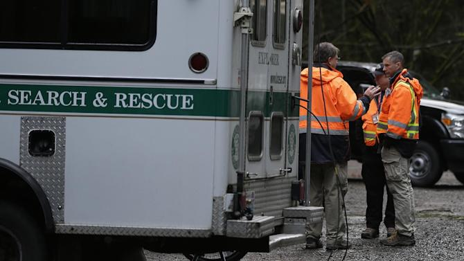 Search and rescue workers gather Friday, Jan. 4, 2013, at the Mount Si trailhead near North Bend, Wash. Searchers in the air and on the ground were looking for 29-year-old Kurt Ruppert of Lake City, Fla., who has been missing since a skydiving trip on Thursday. (AP Photo/Ted S. Warren)