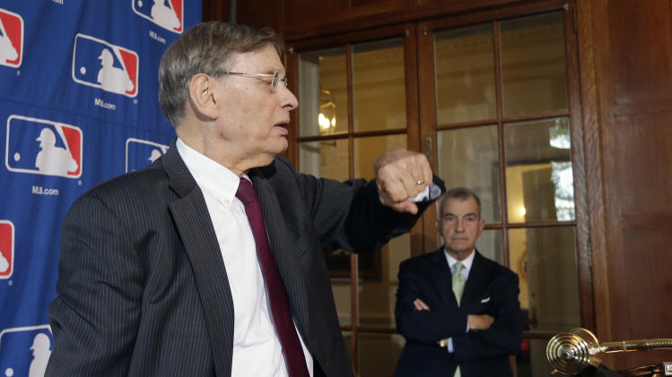Major League Baseball Commissioner Bud Selig checks his watch before a news conference following baseball meetings at the Otesaga Hotel on Thursday, Aug. 15, 2013, in Cooperstown, N.Y. Atlanta Braves President John Schuerholz stands at right. (AP Photo/Mike Groll)