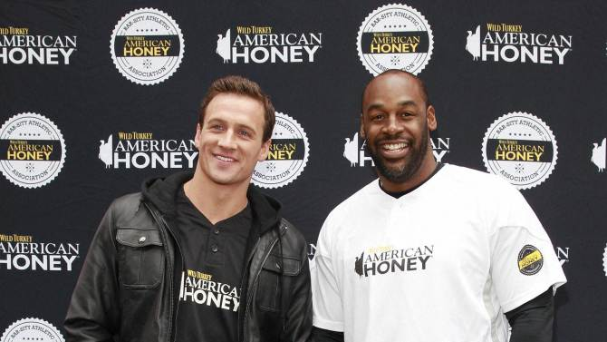 New York :  Eleven time Olympic medalist and TV start Ryan Lochte, left, and pro football legend Donovan McNabb host the first ever American Honey Bar-sity Athletics kickball game in Times Square, on Tuesday, April, 23, 2013 in New York City, New York. AP/PTI(PTI4_24_2013_000140A)