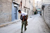 A Syrian rebel carries a comrade who was wounded during clashes in Aleppo on July 31. Syrian President Bashar al-Assad said on Wednesday that the army was fighting for the nation's future as UN officials said the regime was using fighter jets against rebels armed with tanks