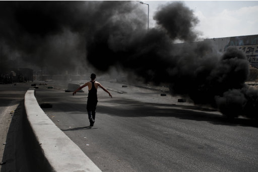 A Palestinian demonstrator walks past burning tires during clashes with Israeli soldiers, not seen, during a protest at the Qalandia checkpoint between the West Bank city of Ramallah and Jerusalem, Wednesday, Sept. 21, 2011. Palestinians clashed with Israeli security forces in Qalandia Wednesday, as thousands of flag-waving Palestinians rallied in towns across the West Bank to show support for their president's bid to win U.N. recognition of a Palestinian state. (AP Photo/Tara Todras-Whitehill)
