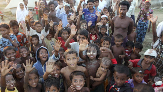 In this photo taken on Oct. 28, 2012, Muslims refugee children wave their hands while taking photos at their refugee camp in Sittwe, Rakhine State, western Myanmar.Authorities in Myanmar's western Rakhine state have imposed a two-child limit for Muslim Rohingya families, a policy that does not apply to Buddhists in the area and comes amid accusations of ethnic cleansing in the aftermath of sectarian violence. (AP Photo/Khin Maung Win)