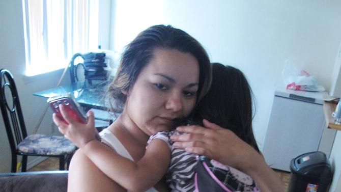 """Melissa Torrez, 27, holds her 4-year-old daughter in her apartment in Albuquerque, N.M., Friday, May 17, 2013. Torrez chased down a man for miles and ran into his car Wednesday, May 15, after he abducted her daughter. She told The Associated Press her """"mother's instincts"""" kicked in when she launched her chase.  Police later arrested 31-year-old David Hernandez and charged him with kidnapping and child abuse. (AP Photo/Russell Contreras)"""