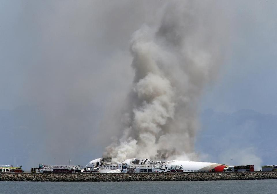 Smokes rises from Asiana Flight 214 after it crashed at San Francisco International Airport in San Francisco, Saturday, July 6, 2013. (AP Photo/Bay Area News Group, John Green)