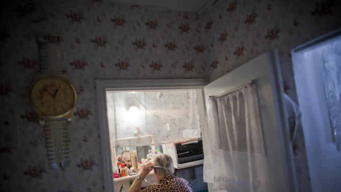 In this Oct. 30, 2012 photo, Tsila Gorenstein, 85, who emigrated to Israel from Moldova in 1993, combs her hair in her apartment in Be'er Sheva, southern Israel. (AP Photo/Oded Balilty)