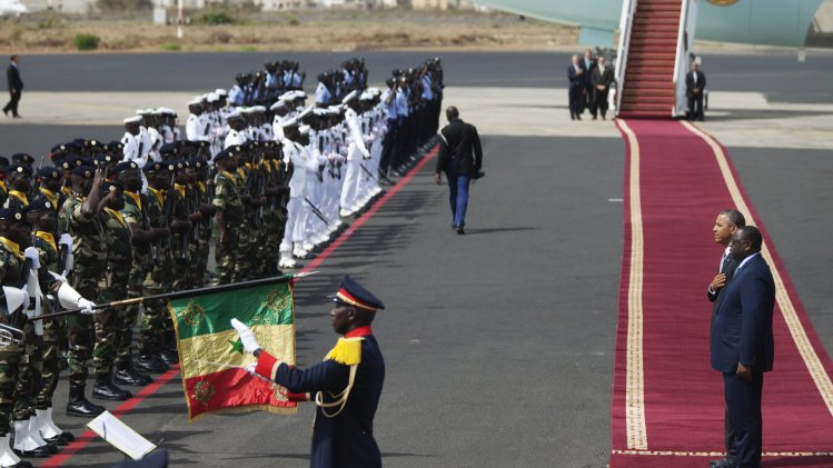 U.S. President Obama and Senegalese President Sall watch military band play the American national anthem at the airport in Dakar