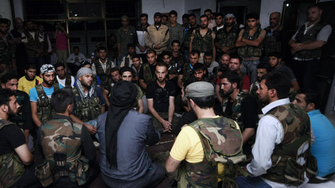 In this Sunday, July 29, 2012 photo, Free Syrian Army soldiers gather at the border town of Azaz, some 20 miles (32 kilometers) north of Aleppo, Syria. The U.N. said 200,000 Syrians have fled the embattled city of Aleppo since intense clashes between regime forces and rebels began 10 days ago. The government forces turned mortars, tank and helicopter gunships against rebel positions on Monday, July 30, 2012. (AP Photo/Turkpix)