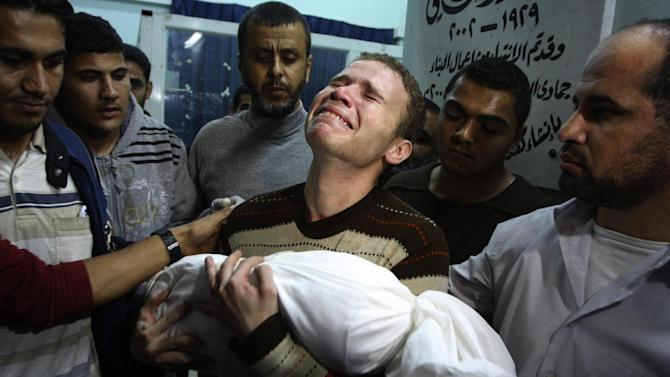 FILE - In this Nov. 14, 2012 file photo, Jihad Masharawi weeps while he holds the body of his 11-month old son Ahmad, at Shifa hospital following an Israeli air strike on their family house, in Gaza City. A U.N. report indicates an errant Palestinian rocket, not an Israeli airstrike, likely killed the baby of Masharawi during fighting in the Hamas-ruled territory last November. The death of Omar al-Masharawi, became a symbol of what Palestinians see as Israeli aggression during eight days of fighting that killed more than 160 Palestinians and six Israelis. (AP Photo/Majed Hamdan, File)