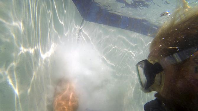 Underwater Unlimited pool repairman Cody McCain applies a special compound as he works on fixing a crack in a backyard pool in Oceanside
