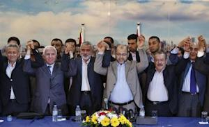 Senior Fatah official Azzam Al-Ahmed, head of the Hamas government Ismail Haniyeh, senior Hamas leader Moussa Abu Marzouq, hold their hands after announcing a reconciliation agreement in Gaza City