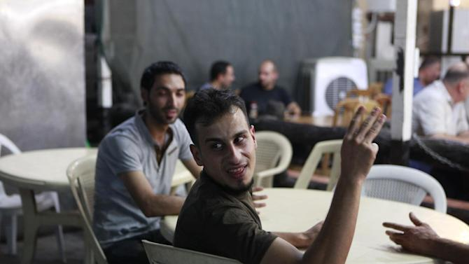 In this Sept. 4, 2012 photo, Abdul Wadud Fawzi, a Sunni man from the former al-Qaida stronghold of Fallujah, sits with his friends in a cafe in Baghdad. Al-Dulaimi has since left the capital to work as a bus driver in Fallujah and Ramadi due to the the recent political crisis. He had to drop out of school to help support his family, earning $300 a month as a driver.  (AP Photo/ Hadi Mizban)