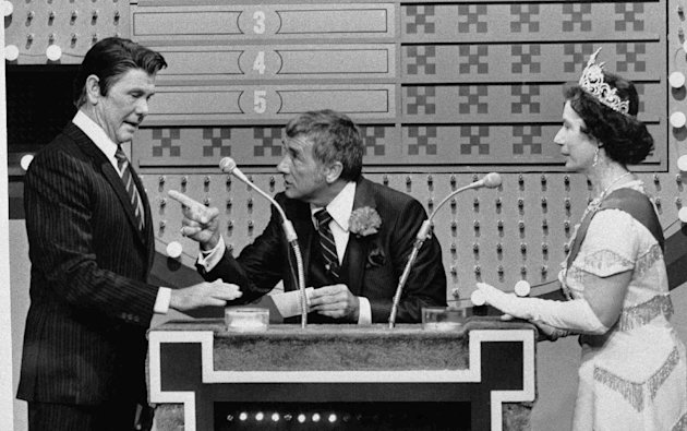 "FILE - In this Nov. 5, 1982 file photo provided by NBC-TV, ""Family Feud"" host Richard Dawson, center, gives President Reagan, played by ""Tonight Show"" host Johnny Carson, a chance at the big money as"