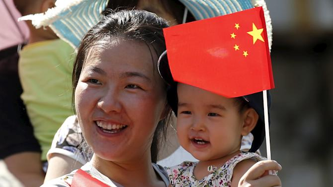 Woman and her baby wait on the street for the performance of military helicopters and planes during the military parade marking the 70th anniversary of the end of World War Two, in Beijing