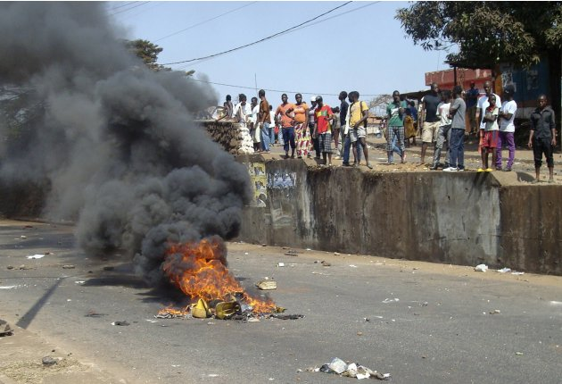 Anti-government protesters set fire during clashes with Guinea security forces in Conakry