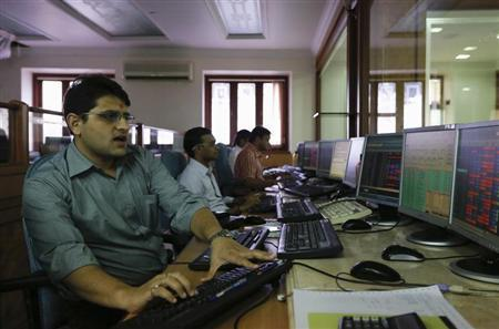 Brokers trade on their computer terminals at a stock brokerage firm in Mumbai