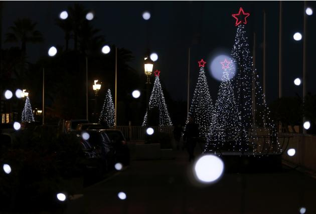 A man walks past Christmas trees in Monte Carlo as Christmas holiday season decorations are displayed in Monaco