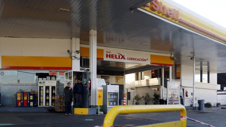 Employees stand at a closed gas station during a 24-hour strike across Argentina in Buenos Aires