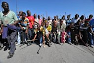 Thousands of South African mine workers walk on September 10 to the Lonmin mine in Marikana to try and stop other miners from going to work. The striking miners claim they earn 4,000 rand a month, while the company says workers already earn around 10,000 rand when bonuses and other compensation are included