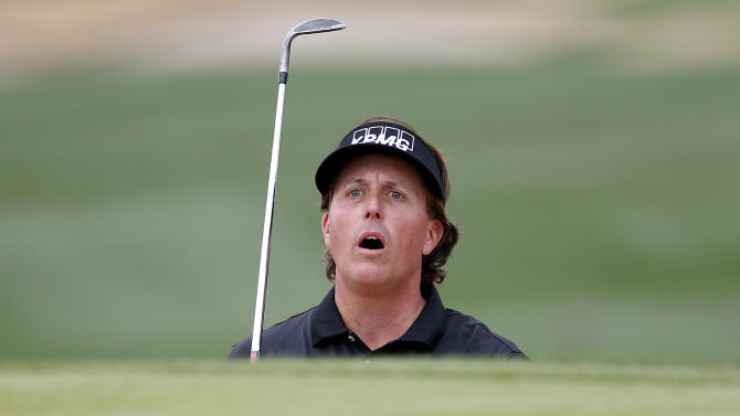 Phil Mickelson watches his second shot land on the 17th green during the final round of the Waste Management Phoenix Open golf tournament on Sunday, Feb. 3, 2013, in Scottsdale, Ariz. Mickelson won the tournament. (AP Photo/Matt York)