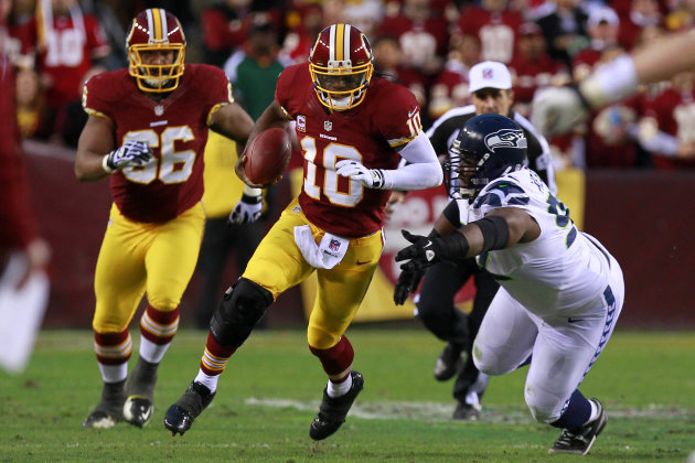 Washington Redskins quarterback Robert Griffin III (10) runs with the ball as Seattle Seahawks defensive tackle Brandon Mebane (92) blocks in first quarter of Redskins and Seahawks at FedEx Field