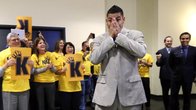 """Seattle Mariners' Felix Hernandez covers his face as he is greeted by front-office staff all wearing yellow """"Kings Court"""" T-shirts before a news conference, Wednesday, Feb. 13, 2013, in Seattle. Hernandez signed a seven-year contract with the Mariners that makes him the highest-paid pitcher in baseball. The new deal will be worth $175 million. (AP Photo/Elaine Thompson)"""