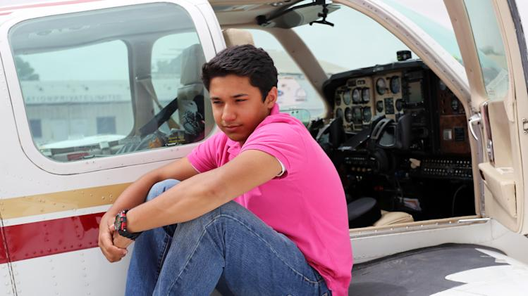 In this July 2014 photo provided by The Citizens Foundation 17-year-old Haris Suleman sits on the wing of his single-engine airplane in Lahore, Pakistan, on his around-the-world flight. The body of the Plainfield, Indiana teen was recovered after his single-engine plane crashed Tuesday, July 22, 2014 shortly after taking off from Pago Pago in American Samoa. Crews were still searching for his father, 58-year-old Babar Suleman, who was flying with him. (AP Photo/Courtesy The Citizens Foundation)