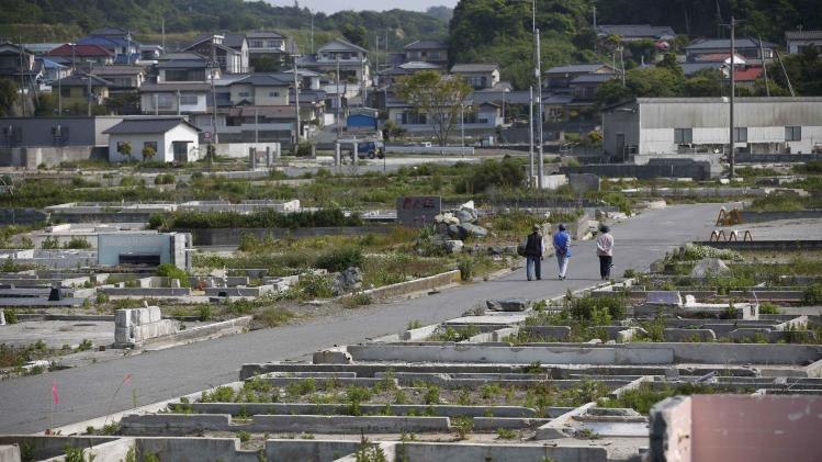 File photo of local residents walking along a street which was devastated by the March 11, 2011 tsunami and earthquake in Iwaki, Fukushima prefecture