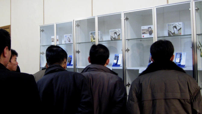 FILE - In this Dec. 16, 2008 file photo, released by China's Xinhua News Agency, people look at 3G mobile phones in Pyongyang, North Korea. North Korea is loosening its restrictions on foreign cellphones and is allowing visitors to bring their own phones into the country. The policy reverses a longstanding rule requiring visitors to relinquish their foreign phones at the border. (AP Photo/Xinhua, Zhang Binyang, File) NO SALES