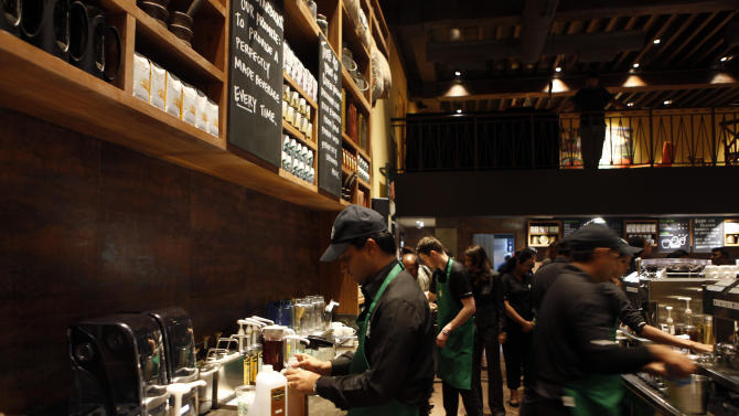 Employees of the newly inaugurated first India outlet of Starbucks work at a counter in Mumbai, India, Friday, Oct. 19, 2012. Starbucks inaugurated its first store in India Friday in a historic building in southern Mumbai as the Seattle-based coffee giant seeks growth in a market long associated with tea drinkers. (AP Photo/Rajanish Kakade)