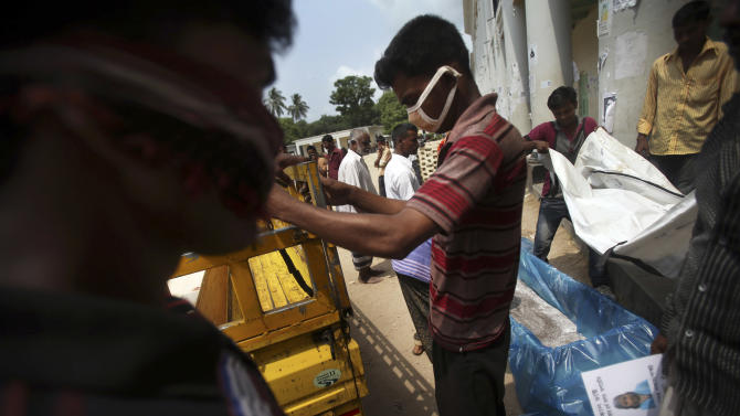 """Workers at a school-turned-morgue place the body of a victim from last week's collapse of a garment factory building into a coffin, Saturday, May 4, 2013 in Savar, near Dhaka, Bangladesh. The death toll in the accident rose to more than 530 on Saturday, a day after the country's finance minister downplayed the impact of the disaster on the garment industry, saying he didn't think it was """"really serious."""" (AP Photo/Wong Maye-E)"""