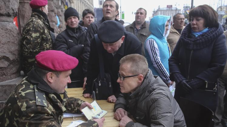 A volunteer speaks with a Ukrainian military officer as he registers for service in the newly-created National Guard in central Kiev