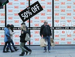 Shoppers pass a sale sign on Oxford Street in central London