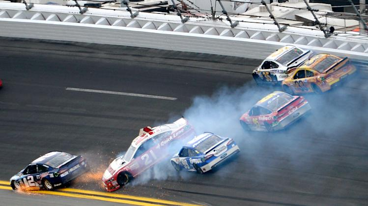 Trevor Bayne (21) spins in Turn 1 as Brad Keselowski (2) hits the apron and Carl Edwards (99), Scott Speed (95), Josh Wise (35) and Austin Dillon (33) try to avoid them during the NASCAR Daytona 500 Sprint Cup Series auto race at Daytona International Speedway in Daytona Beach, Fla., Sunday, Feb. 24, 2013. (AP Photo/Phelan M. Ebenhack)