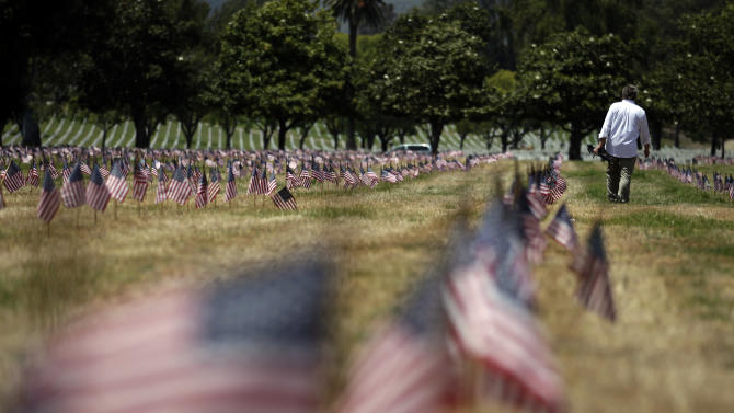 Documentary filmmaker Michael Prescott, right, pays his respects at the Los Angeles National Cemetery in the Westwood section of Los Angeles, Friday, May 25, 2012. (AP Photo/Jae C. Hong)