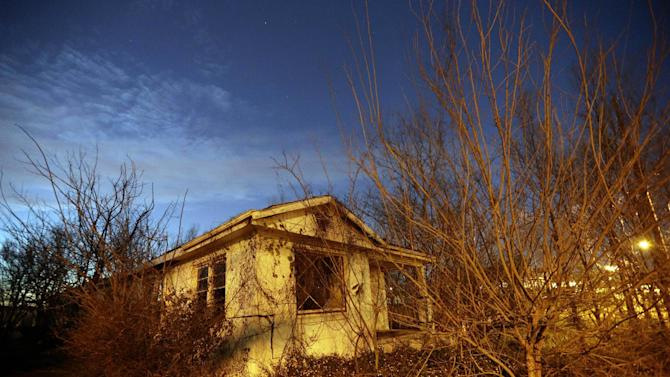 In this Jan. 31, 2013, photo, overgrown vegetation surrounds a damaged house at dusk in the Lower Ninth Ward of New Orleans, a neighborhood that was hit hard by floodwaters from a levee break after Hurricane Katrina. The glittering party in the French Quarter is going stronger than ever. But as revelers celebrate the ultimate comeback from those dark days in 2005, there are still areas of New Orleans that do not look much different than they did right after Hurricane Katrina swept through. (AP Photo/Patrick Semansky)