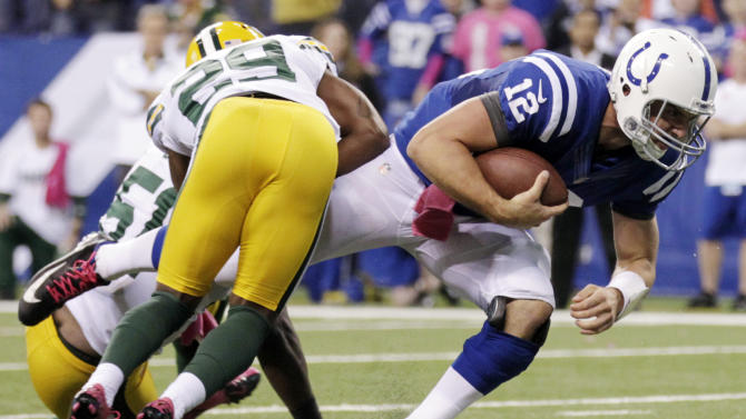 Indianapolis Colts quarterback Andrew Luck (12) dives for a first down as he is tackled by Green Bay Packers cornerback Casey Hayward during the second half of an NFL football game in Indianapolis, Sunday, Oct. 7, 2012.  The Colts won 30-27. (AP Photo/AJ Mast)