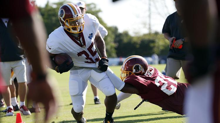 Washington Redskins running back Lache Seastrunk is brought down by cornerback Richard Crawford during practice at the team's NFL football training facility, Monday, July 28, 2014 in Richmond, Va