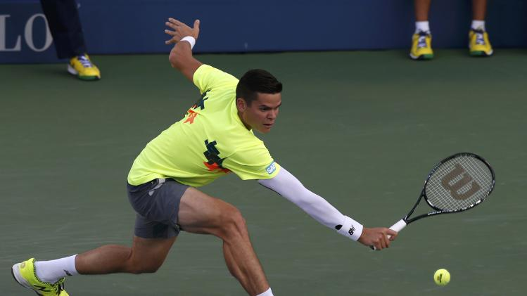 Milos Raonic of Canada hits a return to Peter Gojowczyk of Germany during their match at the 2014 U.S. Open tennis tournament in New York