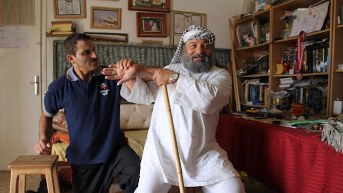 In this June 30, 2012 photo Mohammed Moncef Ouerghi, who developed an Islamic form of martial arts called Zamaqtel favored by Salafis, twists the wrist of his assistant during an interview in his office in Tunis. Tunisia's hardcore Salafis' frequent protests against perceived insults to Islam, especially by artists, have rocked the country and succeeded in mobilizing disaffected and angry youth much more effectively than secular opposition parties. (AP Photo/Paul Schemm)