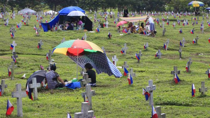 Families sit on the ground as they picnic near tombstones at a military camp in Taguig City
