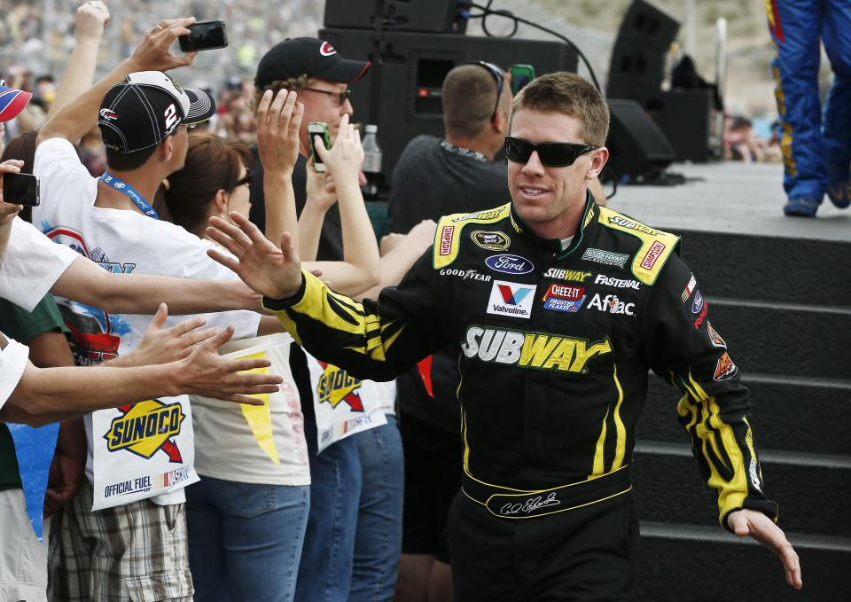 Carl Edwards high-fives fans during driver introductions before the NASCAR Sprint Cup Series auto race, Sunday, March 3, 2013, in Avondale, Ariz. (AP Photo/Ross D. Franklin)