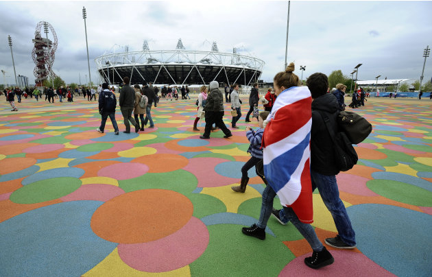 A fan draped in a union flag makes her way past the Olympic Stadium inside the Olympic Park in London