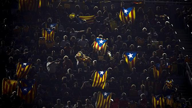 """FILE- In this Oct. 7, 2012, file photo, people hold pro-independence Catalonian flags at the Camp Nou stadium during a Spanish La Liga soccer match between Real Madrid and FC Barcelona in Barcelona, Spain. More than ever, FC Barcelona, known affectionately as Barca, lived up to its motto of being """"more than a club"""" for this wealthy northeastern region where Spain's economic crisis is fueling separatist sentiment. Barca has been seen as a bastion of Catalan identity dating back to the three decades of dictatorship when Catalans could not openly speak, teach or publish in their native Catalan language. Barcelona writer Manuel Vazquez Montalban famously called the football team """"Catalonia's unarmed symbolic army.""""(AP Photo/Daniel Ochoa De Olza, File)"""