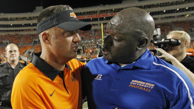 FILE- In this Sept. 1, 2012, file photo, Oklahoma State head coach Mike Gundy, left, and Savannah State head coach Steve Davenport, right, talks at midfield following OSU's 84- win in an NCAA college football game in Stillwater, Okla. Don't celebrate the end of those David vs. Goliath matchups in college football just yet. But part of the fallout of what could be sweeping changes coming to college sports would be a decrease in those sorts of games, where power football schools pad their records and smaller colleges reap big paydays. (AP Photo/Sue Ogrocki, File)
