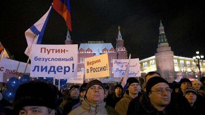 "People rally in support of Russian Prime Minister and presidential candidate Vladimir Putin following an election day, outside the Kremlin in Moscow, Sunday, March 4, 2012. Vladimir Putin has claimed victory in Russia's presidential election, which the opposition and independent observers say has been marred by widespread violations. Putin made the claim at a rally of tens of thousands of his supporters just outside the Kremlin, thanking his supporters for helping foil foreign plots aimed to weaken the country. Posters read ""Putin is indisputable leader,"" ""We believe in Russia."" (AP Photo/Harry Engels)"
