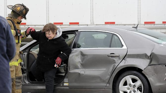 A firefighter helps a woman out of a car as emergency personnel responds to a multi-vehicle accident on Interstate 75  in Detroit, Thursday, Jan. 31, 2013. Snow squalls and slippery roads led to a series of accidents that left at least three people dead and 20 injured on a mile-long stretch of southbound I-75. More than two dozen vehicles, including tractor-trailers, were involved in the pileups. (AP Photo/The Detroit News, David Coates)