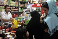 <p>Iranian women shops at a grocery store in Tehran in September 2012. Iran's currency, the rial, slipped another four percent on Tuesday to close at 36,100 to the dollar, according to exchange tracking websites.</p>