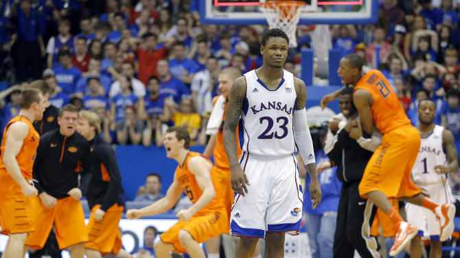 Kansas' Ben McLemore walks off the court as Oklahoma State players celebrate their victory in an NCAA college basketball game in Lawrence, Kan. on Saturday, Feb. 2, 2013. (AP Photo/The Wichita Eagle, Travis Heying)